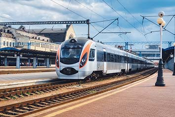 High speed train at the railway station in ukraine. modern intercity train on the railway platform. urban scene with railroad, buildings and blue cloudy sky