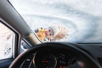 The kid helps and scraping snow and ice from car window