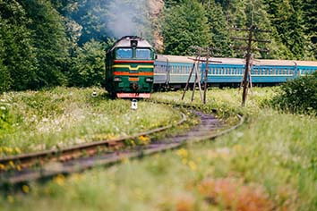 Locomotive with wagons riding railroad in carpathian mountains. train with passengers turning on railway. travel and tourism