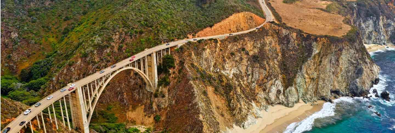 Beautiful aerial shot of green hills and a curvy narrow bridge going along the cliffs