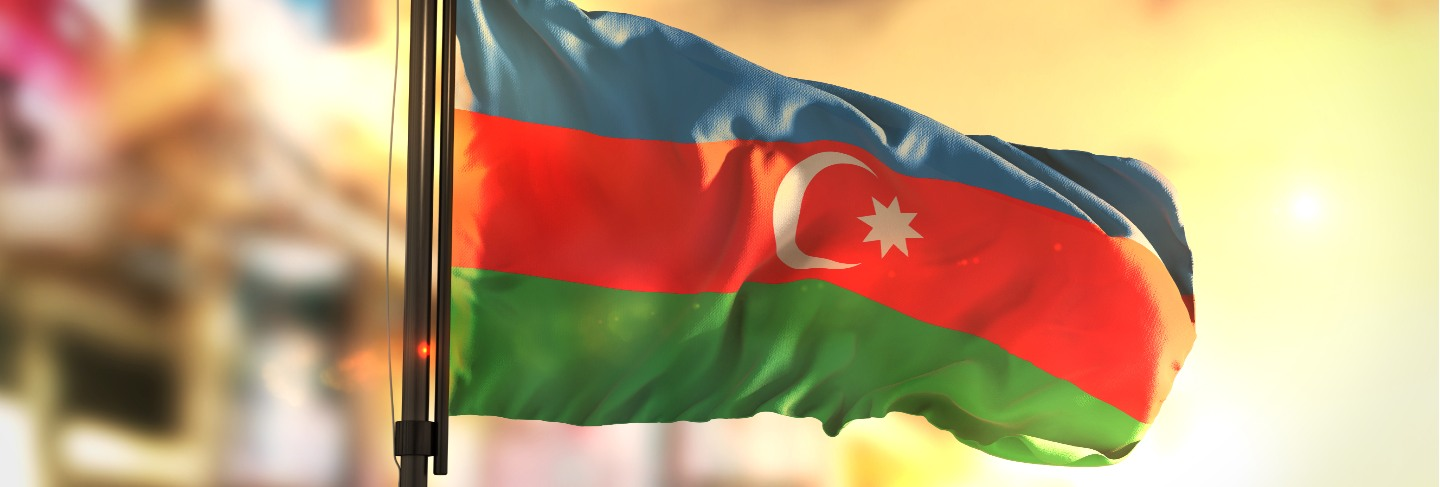 Azerbaijan flag against city blurred background at sunrise backlight