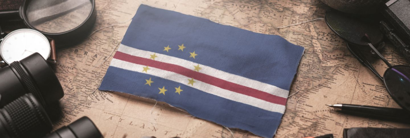 Cape verde flag between traveler's accessories on old vintage map. tourist destination concept.