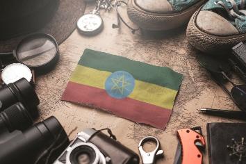 Ethiopia flag between traveler's accessories on old vintage map. tourist destination concept.