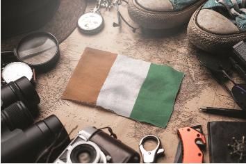 Ivory coast flag between traveler's accessories on old vintage map. tourist destination concept