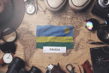 Rwanda flag between traveler's accessories on old vintage map