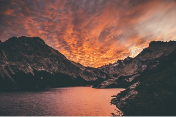 Beautiful shot of the sunset in the mountains by the lake with amazing clouds