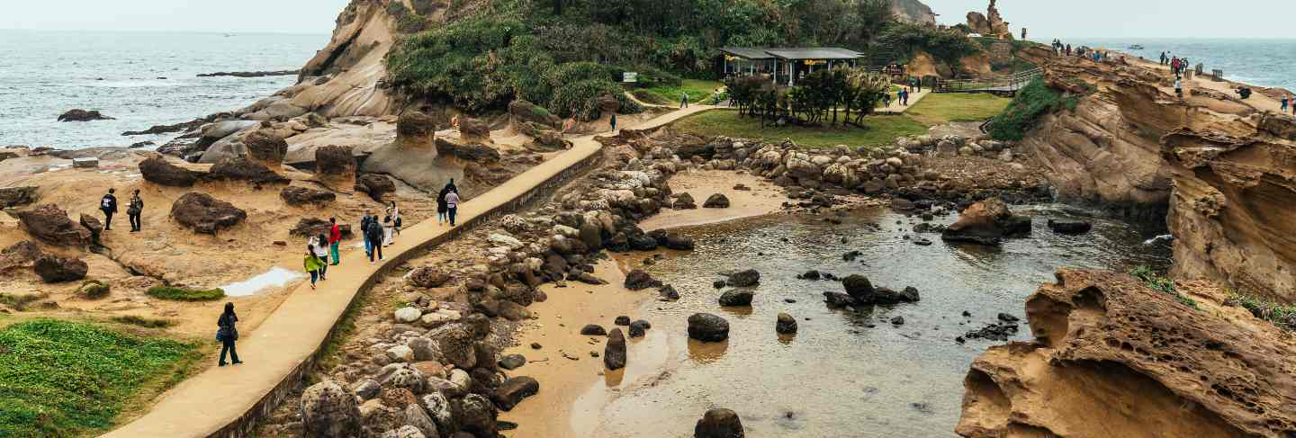 Aerial view diversity of tourists walking in yehliu geopark, a cape on the north coast of taiwan. a landscape of honeycomb and mushroom rocks eroded by the sea.