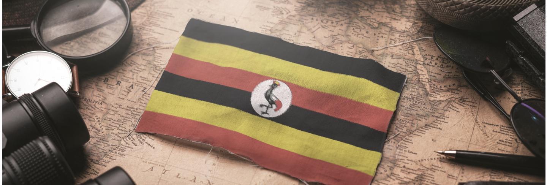 Uganda flag between traveler's accessories on old vintage map. tourist destination concept.