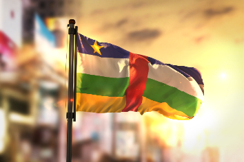 Central african republic flag against city blurred background at sunrise backlight
