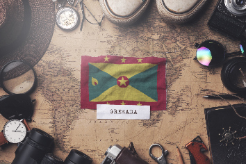 Grenada flag between traveler's accessories on old vintage map. overhead shot