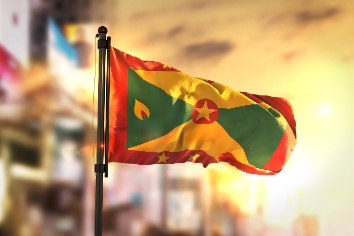 Grenada flag against city blurred background at sunrise backlight