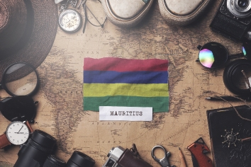Mauritius flag between traveler's accessories on old vintage map. overhead shot