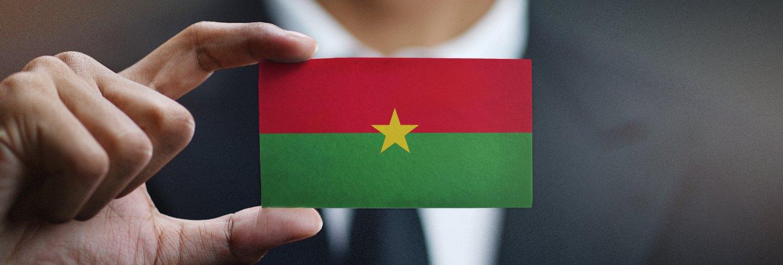 Businessman holding card of burkina faso flag