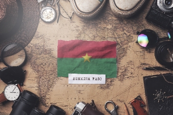 Burkina faso flag between traveler's accessories on old vintage map. overhead shot