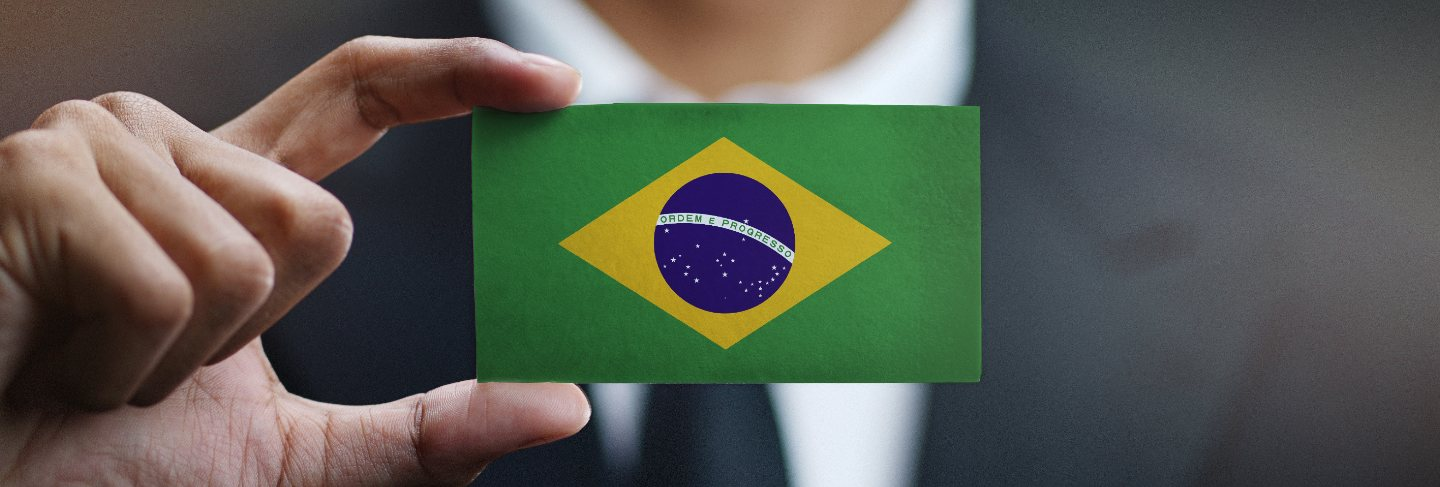 Businessman holding card of brazil flag