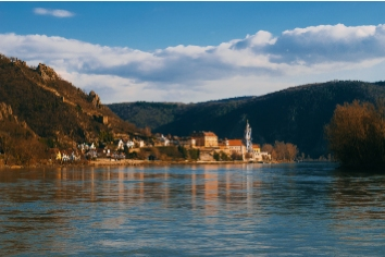 Photo of a small village bathed in sunlight near danube river in austria. places t see while traveling.