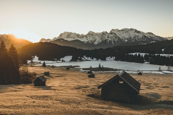 Long range shot of a valley with a hut house and tall snowy mountains