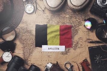 Belgium flag between traveler's accessories on old vintage map. overhead shot