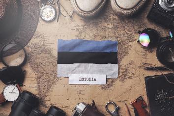 Estonia flag between traveler's accessories on old vintage map. overhead shot