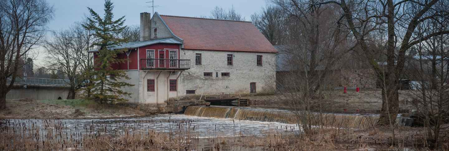 Old mill on the river bank with small waterfall at winter time
