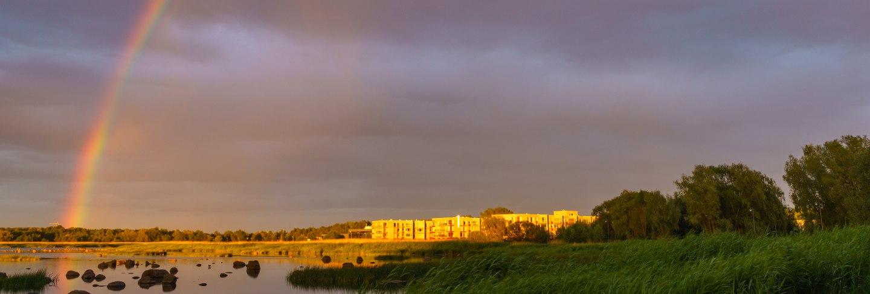 Rainbow over stony seacoast by sunset