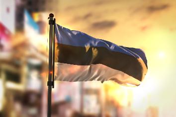 Estonia flag against city blurred background at sunrise backlight