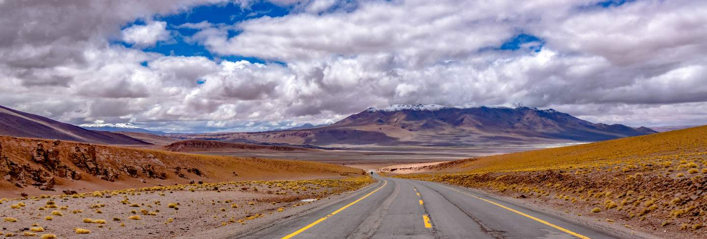 Road in atacama desert savanna, mountains and volcano landscape, chile, south america