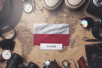 Poland flag between traveler's accessories on old vintage map. overhead shot