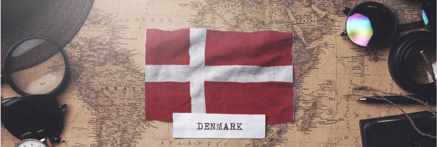 Denmark flag between traveler's accessories on old vintage map