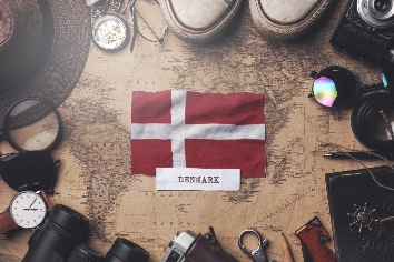 Denmark flag between traveler's accessories on old vintage map