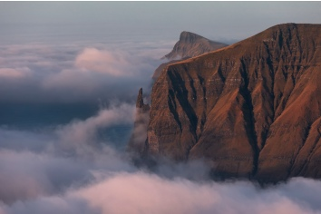 Rock witch's finger at dawn. clouds covered the atlantic ocean. faroe islands, europe.