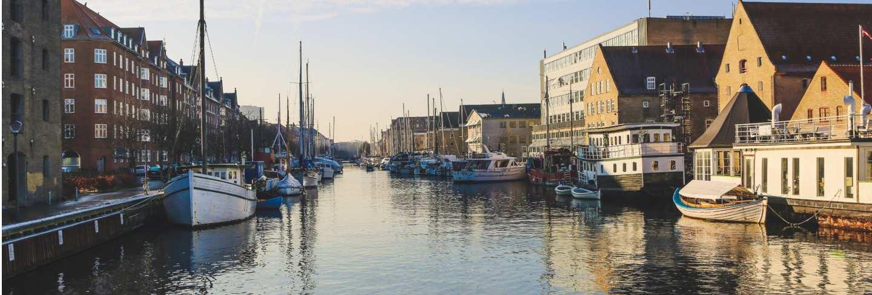 Wide shot of boats on the body of water near buildings in christianshavn, copenhagen,