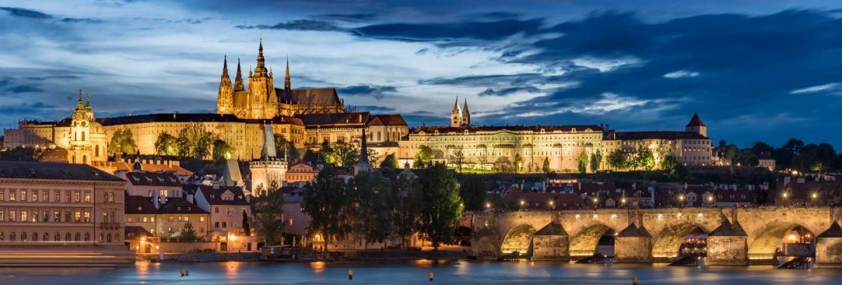 Prague castle with cloudy sunset blue sky and charles bridge light up