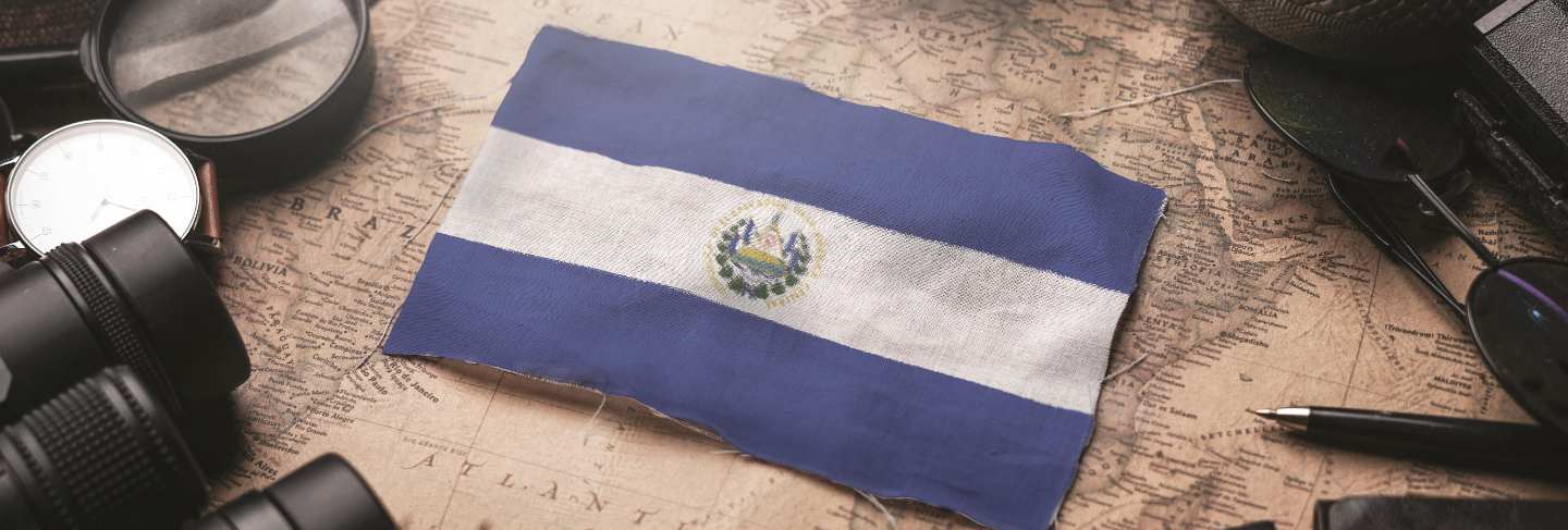 El salvador flag between traveler's accessories on old vintage map