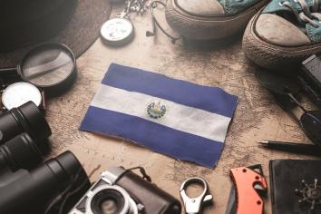El salvador flag between traveler's accessories on old vintage map