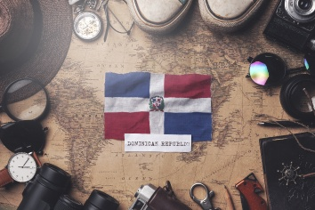 Dominican republic flag between traveler's accessories on old vintage map