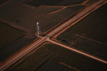 Beautiful aerial shot of narrow roads intersection in the countryside with a white tower