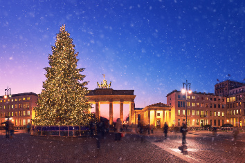 Brandenburg gate in berlin with christmas tree and falling snow in the evening
