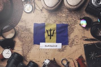 Barbados flag between traveler's accessories on old vintage map.