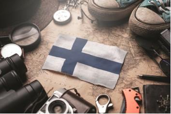 Finland flag between traveler's accessories on old vintage map. tourist destination concept