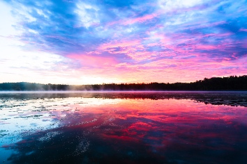 Bright colorful foggy sunset on the lake with clouds and reflections