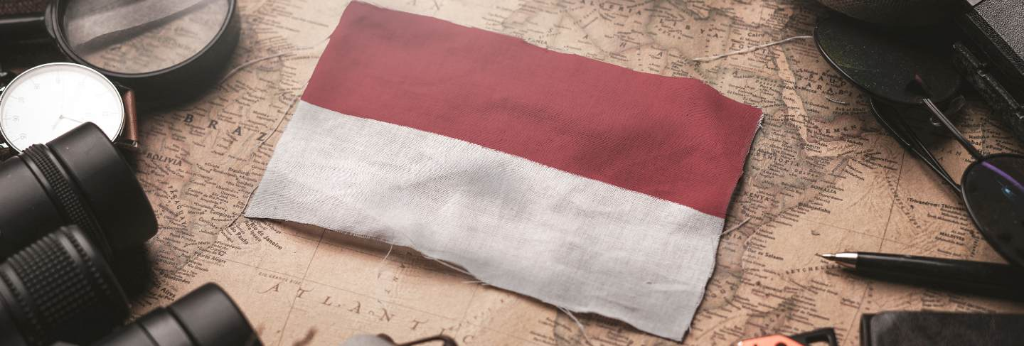 Indonesia flag between traveler's accessories on old vintage map. tourist destination concept