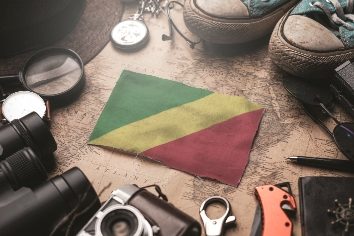 Republic of the congo flag between traveler's accessories on old vintage map. tourist destination concept.