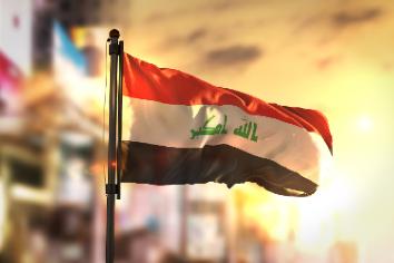 Iraq flag against city blurred background at sunrise backlight