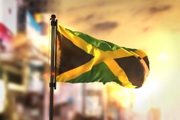 Jamaica flag against city blurred background at sunrise backlight