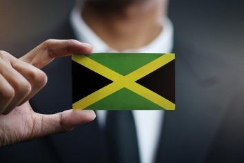 Businessman holding card of jamaica flag