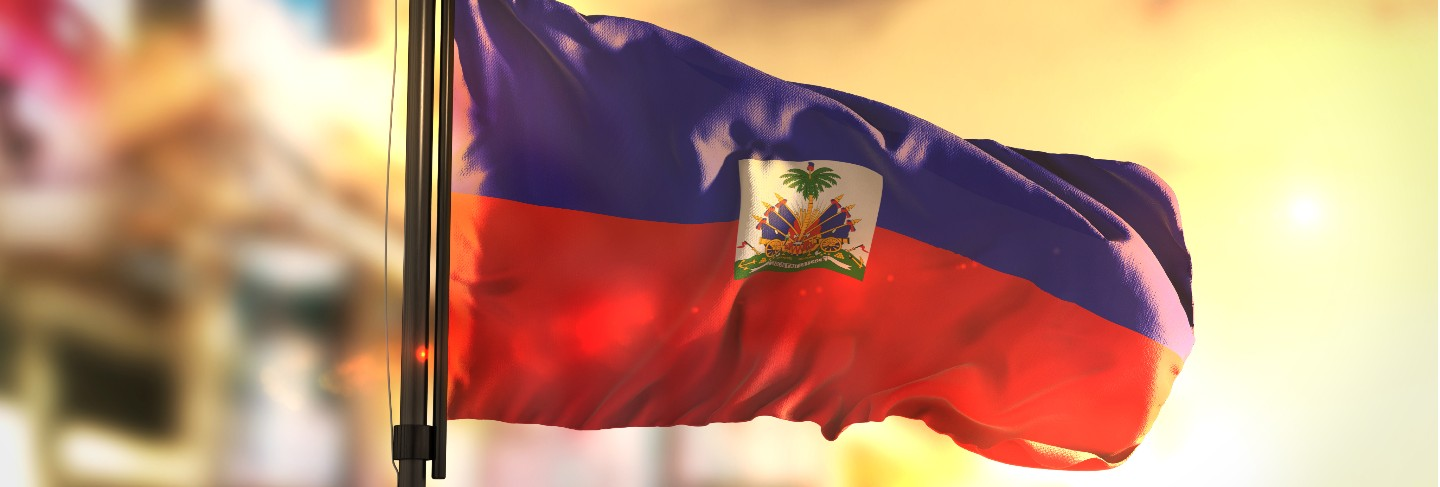 Haiti flag against city blurred background at sunrise backlight