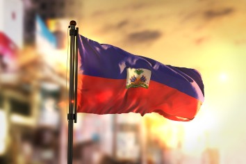 Haiti flag against city blurred background at sunrise backlight