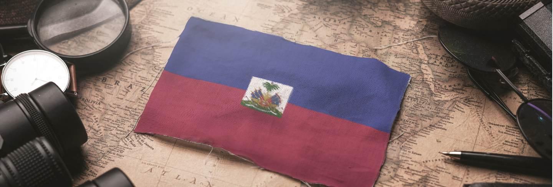 Haiti flag between traveler's accessories on old vintage map. tourist destination concept.