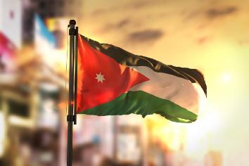 Jordan flag against city blurred background at sunrise backlight